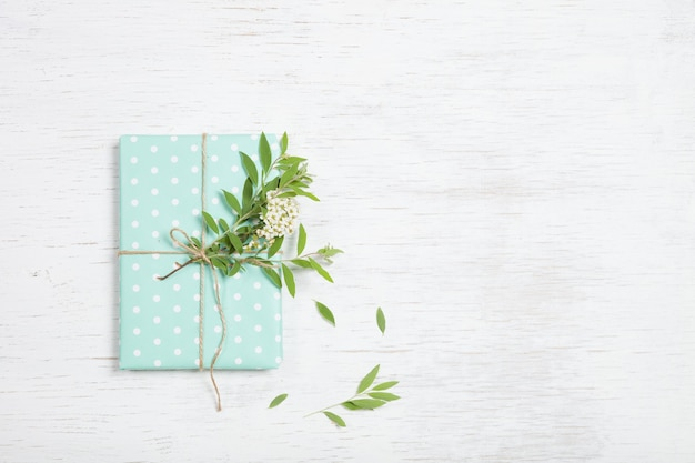 庭の木の枝と花とターコイズブルーの紙で飾られた誕生日プレゼントの上面図