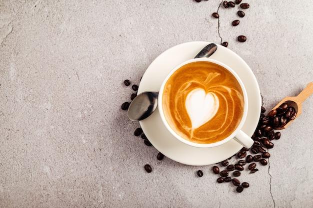 コンクリートの背景に白いカップで飾られたカプチーノコーヒーの上面図