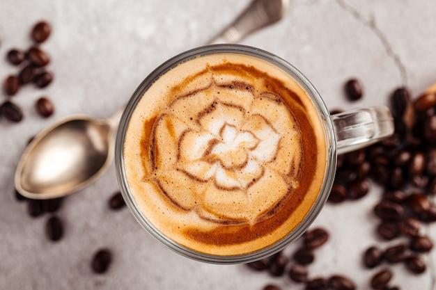 Вид сверху на украшенный кофейный латте в стеклянной кружке на бетонном фоне