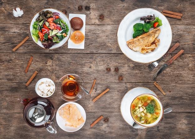 木製テーブルのさまざまな料理の3コースメニューの上面図