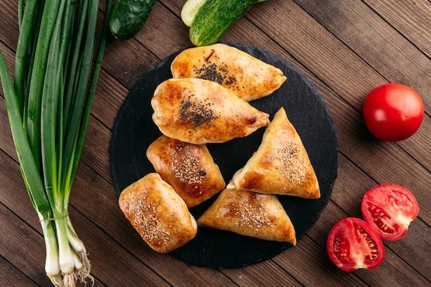 黒石のプレートに肉のサムサとさまざまな東洋の焼きパイの上面図