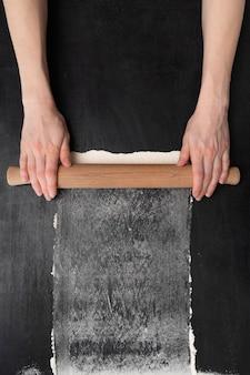 小麦粉とテーブルの上に木製の麺棒で女性の手の上面図