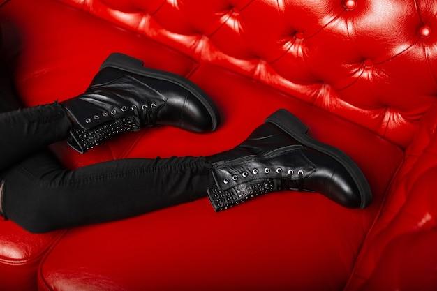 Вид сверху на женские ножки в винтажных джинсах в модных кожаных черных ботинках на шнуровке. закройте вверх сезонной женской обуви. осень зима. стиль.