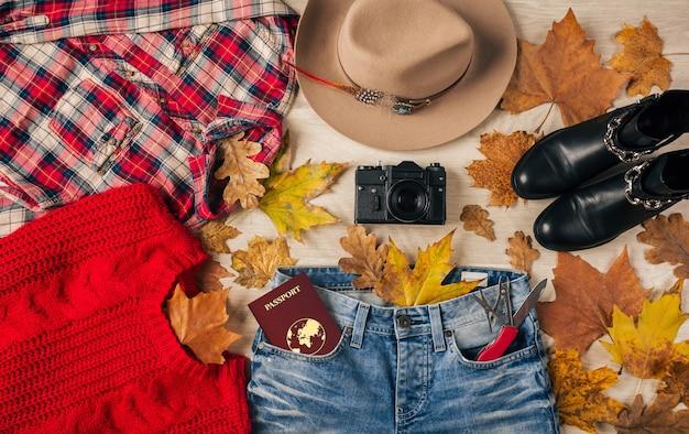 女性スタイルのアクセサリー、赤いセーター、市松模様のフランネルシャツ、ジーンズ、黒い革のブーツ、秋のファッショントレンド、ビンテージフォトカメラ、スイスナイフ、パスポート、旅行者の服のフラットレイの上面図