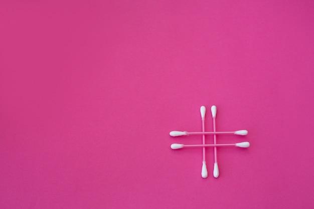 ピンクの背景に十字形に配置された白い頭を持つ4つのピンクの綿棒の上面図。