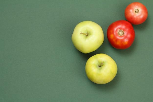 녹색 배경에 신선한 사과와 토마토에 대한 상위 뷰. 식탁에 야채와 과일입니다.