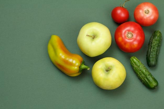 녹색 배경에 신선한 사과, 피망, 토마토, 오이에 대한 상위 뷰. 식탁에 야채와 과일입니다.