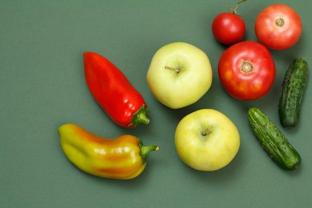 녹색 배경에 신선한 피망, 사과, 토마토, 오이에 대한 상위 뷰. 식탁에 야채와 과일입니다.