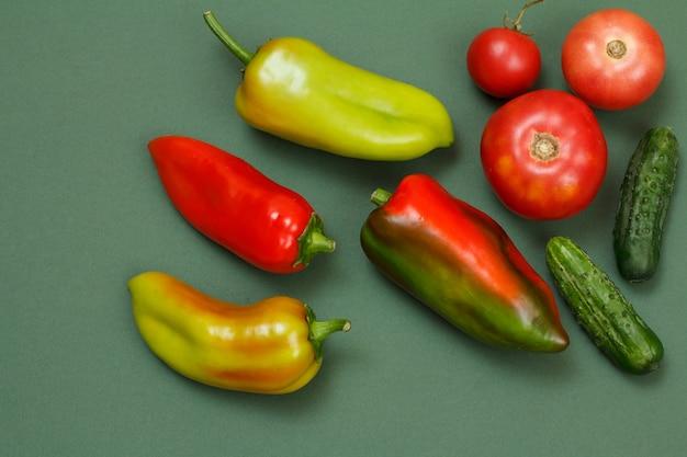 緑の背景に新鮮なピーマン、トマト、きゅうりの上面図。台所のテーブルの上の野菜や果物。
