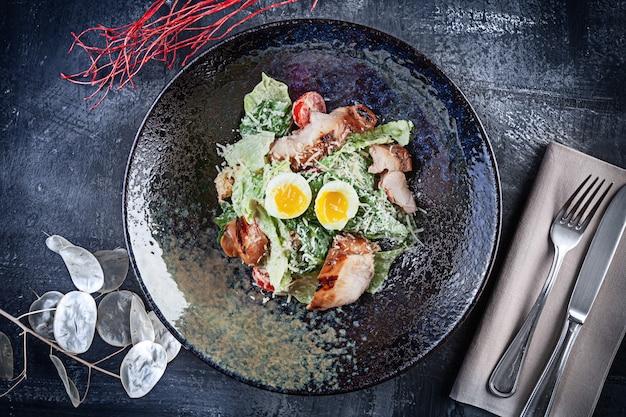 暗い石の背景に新鮮なサラダボウルの平面図です。コピースペースとlucnhのフラットレイアウトの食品。メニューの写真。モダンシーザーサラダ