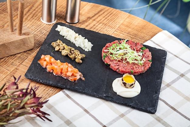 暗い石のプレートにソースと生のウズラの卵、ケッパー、トマト、みじん切り玉ねぎを添えて新鮮なタルタルステーキの上面図。セレクティブフォーカス。デザインのスペースをコピーします。メニューの写真