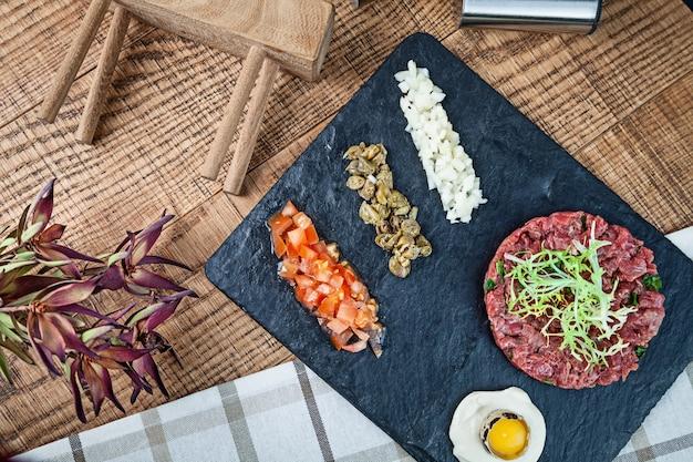 Вид сверху на свежий стейк из говядины тартар, подается на темной каменной тарелке с соусом и сырым перепелиным яйцом, каперсами, помидорами и нарезанным луком
