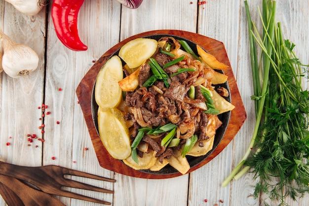 軽い木製のテーブルの上の鋳鉄鍋で牛肉とネギとフライドポテトの上面図