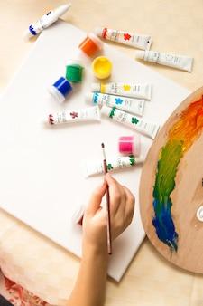 Вид сверху на девушку, держащую кисть и рисунок масляными красками
