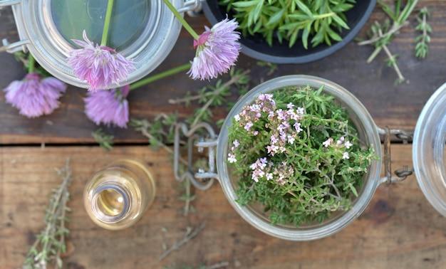 Вид сверху на стеклянную банку, полную ароматических трав и масла бутылки на деревянный стол