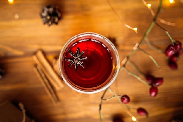 Вид сверху на стеклянную кружку черного чая с звездчатым анисом на деревянном праздничном столе