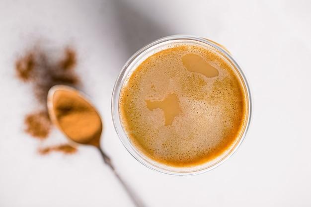 Вид сверху на стакан кофе латте с корицей