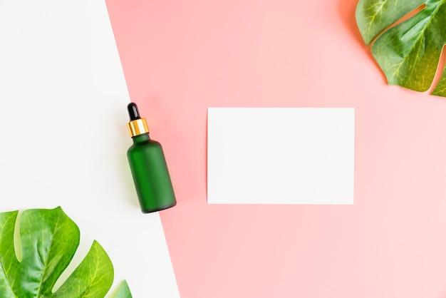 Вид сверху на крем из зеленой бутылки и заметку, макет бренда косметической продукции