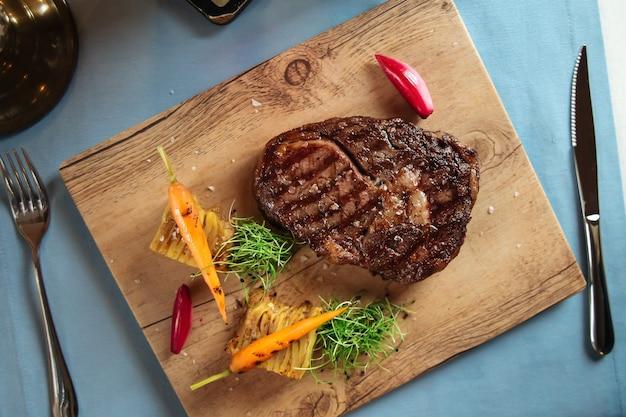 Вид сверху на стейк рибай из говядины с картофелем на деревянной доске