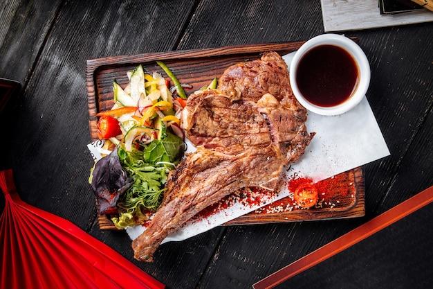 Вид сверху на сочный ковбойский стейк на гриле с салатом