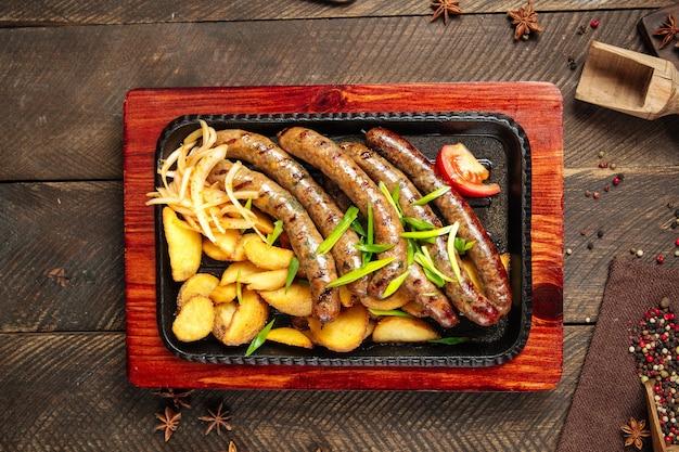 Вид сверху на колбаски гриль с картофелем