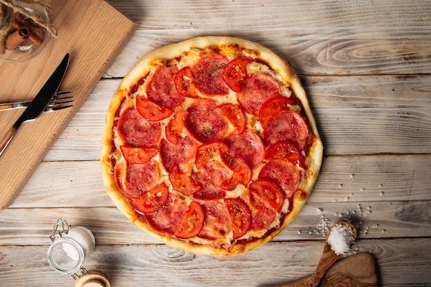 木製のテーブルに乾燥ハーブとトマトのハムピザの上面図