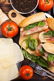 Вид сверху на здоровые бутерброды рядом с ингредиентами, из которых они сделаны на деревянном столе