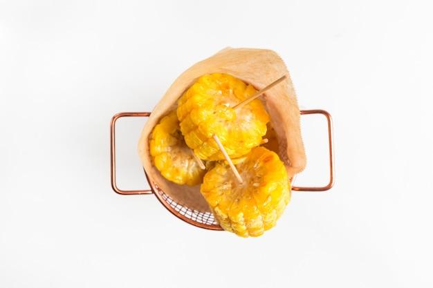 紙で銅のバケツに孤立した調理済みカットコーンのトップビュー