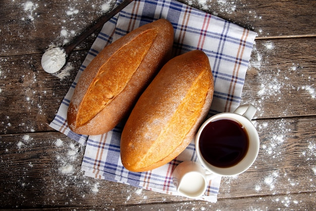 木製のまな板にコーヒーとパンの上面図