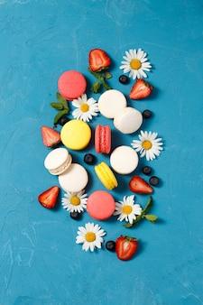 Вид сверху на миндальное печенье, клубнику и ромашки