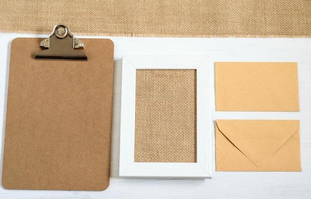 Вид сверху на макет фотографии с доской сзажимом для бумаги, рамкой для рисунка, конвертами и тканью из мешковины на белом фоне.