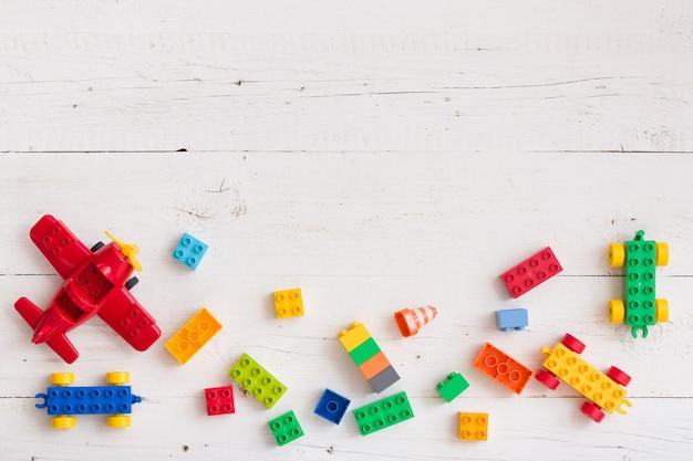 Вид сверху на многоцветные игрушечные кирпичи на белом деревянном фоне
