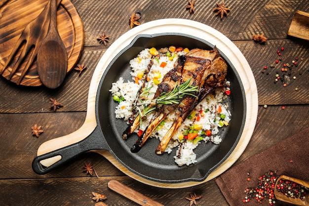 Вид сверху на бараньи ребрышки с овощами и рисом в чугунной сковороде на деревянном столе