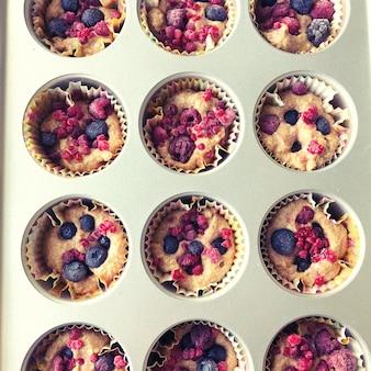 ベーキングパンにベリーと焼きたてのカップケーキの上面図。健康的な食事と家庭での料理の概念。