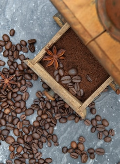 灰色の大理石の背景にスパイスとコーヒーと豆でいっぱいの古いコーヒーグラインダーの上面図
