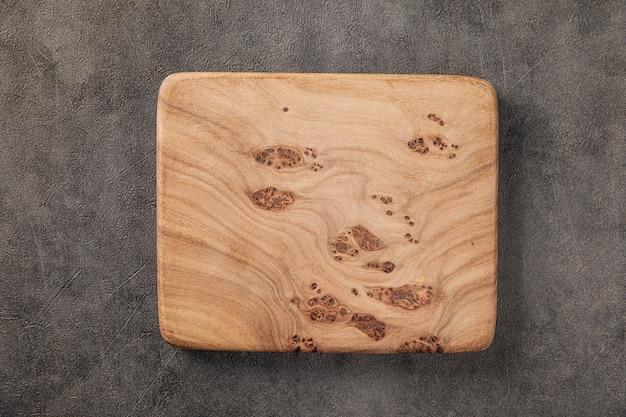 Вид сверху на оливковую деревянную сервировочную доску на сером