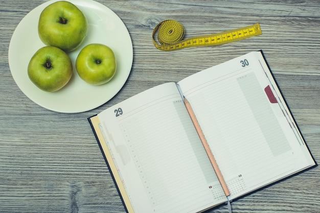 열린 공책과 연필에 대한 상위 뷰, 사과가 있는 tlape 및 회색 나무 배경에 테이프 측정