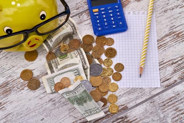 お金の山、電卓と木製のテーブルの上のペンで貯金箱のトップビュー