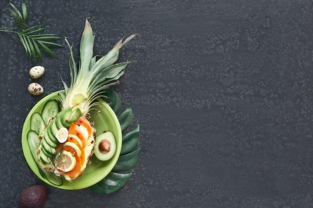 Вид сверху на ананасную лодочку с копченым лососем и ломтиками авокадо с лимоном и перепелиным яйцом