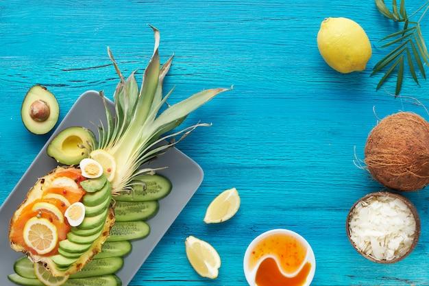 Вид сверху на лодочку с копченым лососем, авокадо, лимоном и перепелиными яйцами