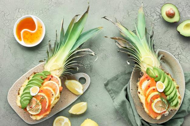 Вид сверху на ананасную лодку с копченым лососем, авокадо, лимоном и перепелиными яйцами