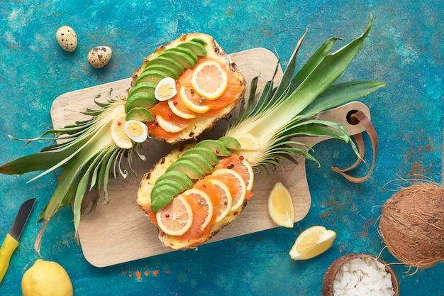 Вид сверху на лодочки-ананасы с ломтиками копченого лосося и авокадо с лимоном и перепелиными яйцами, плоская кладка на текстурированной стене