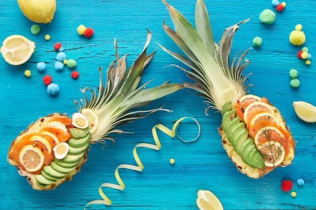 Вид сверху на ананасы с копченым лососем и ломтиками авокадо с лимоном и перепелиными яйцами