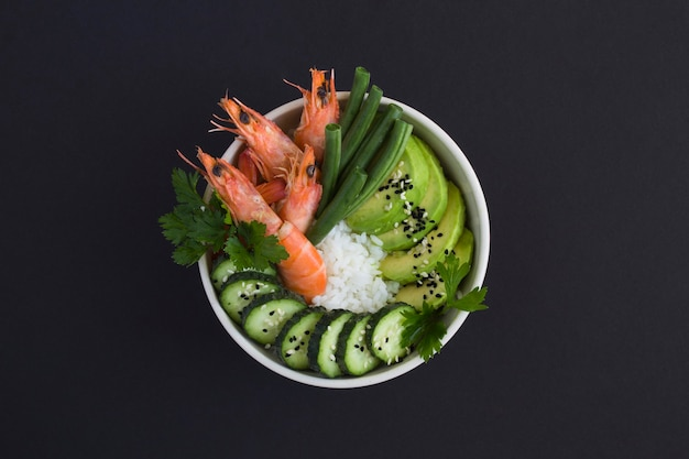 검정색 배경에 있는 흰색 그릇에 붉은 새우와 녹색 야채를 넣은 포케 샐러드의 최고 전망. 확대.
