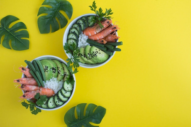 열대 배경에 있는 흰색 그릇에 붉은 새우와 녹색 채소를 넣은 포케 샐러드의 최고 전망. 공간을 복사합니다.