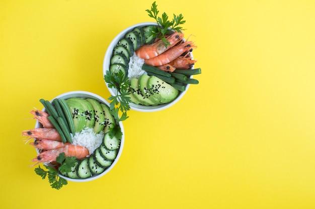 노란색 배경에 있는 흰색 그릇에 붉은 새우와 녹색 채소를 넣은 포케 샐러드의 최고 전망. 공간을 복사합니다.