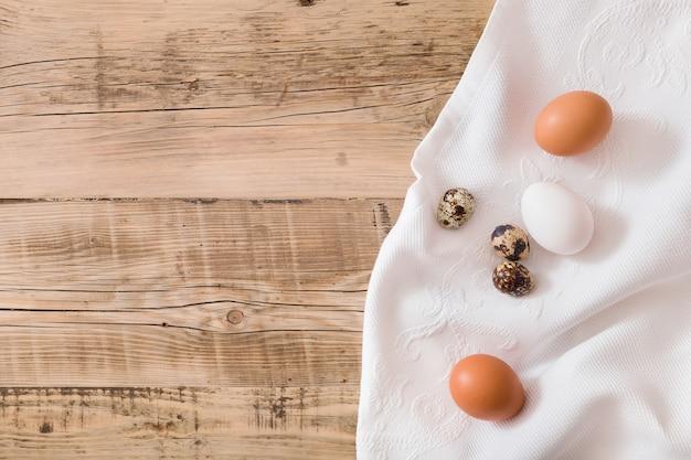 木製の背景とテキスタイルのウズラの卵の上面図