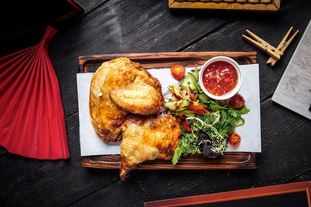 Вид сверху на жареный цыпленок с соусом и зеленью на деревянной доске