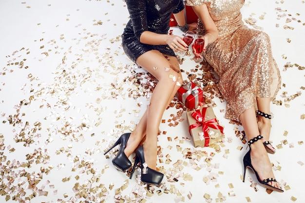 輝く金色の紙吹雪、ギフトボックス、シャンパングラスを背景にセクシーな女性の脚の上面図。キラキラ光るイブニングドレスを着ています。時間を祝う。
