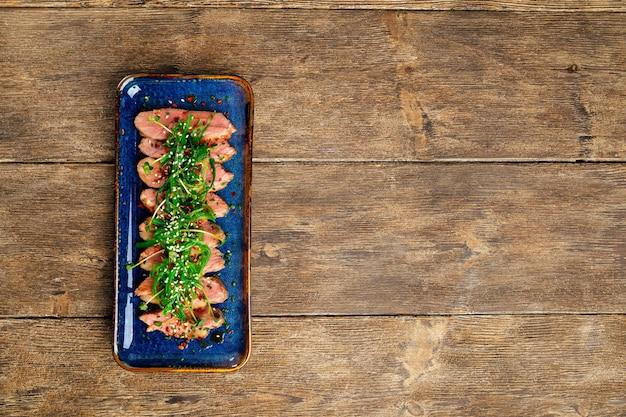 木製の背景に海藻チュカとスライスした乾燥熟成ロースト鴨胸肉の上面図